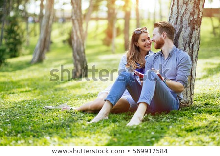 Happy couple of students with a notebook sitting on grass at cam Stock photo © HASLOO