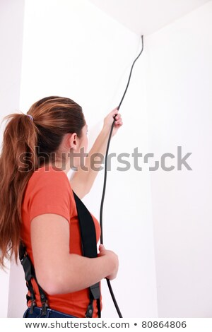 handywoman pulling a black wire coming from the ceiling Stock photo © photography33