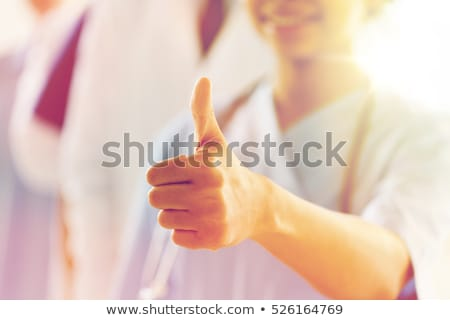 Female Doctor showing thumbs up sign stock photo © get4net