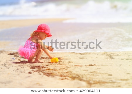Stockfoto: Little Girl Playing On The Sea Shore Sea