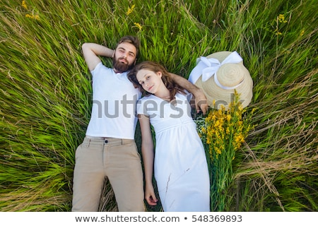 man with hat  laying down on  field and smiles Stock photo © feedough