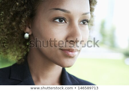 Stock photo: Closeup portrait of a young pensive african-american businessman over dark background