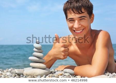 teenager boy creates pyramid from pebble on stony seacoast at ni Stock photo © Paha_L