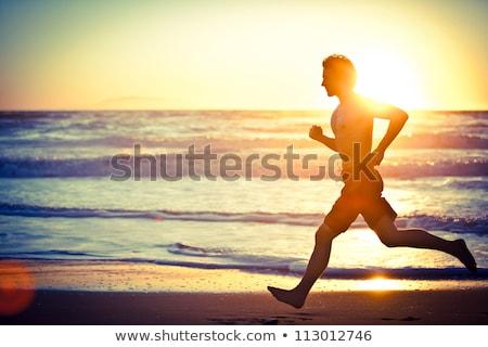 Przystojny mężczyzna sportowiec uruchomiony plaży młodych Zdjęcia stock © deandrobot