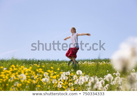Girl riding unicycle through meadow Stock photo © IS2