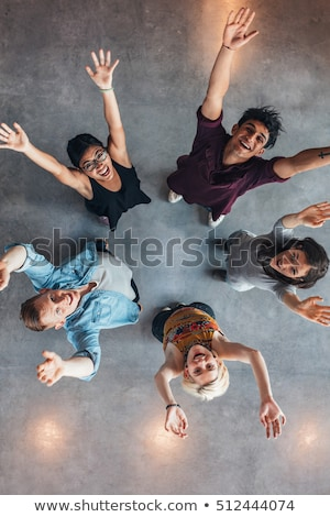 Smiling woman raising arms overhead Stock photo © IS2