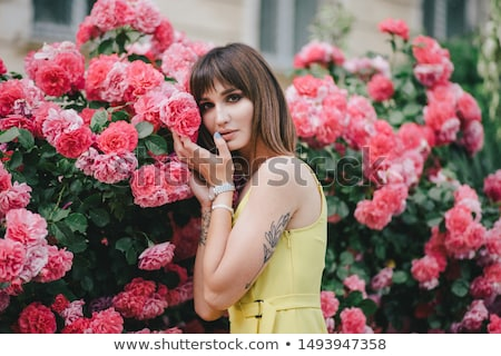 Pink flower in a girl's hand with a tattoo . Young stylish girl in high-heeled shoes, and jeans on a Stock photo © artjazz