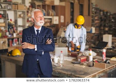 Businesman standing with tool on his hand Stock photo © ra2studio