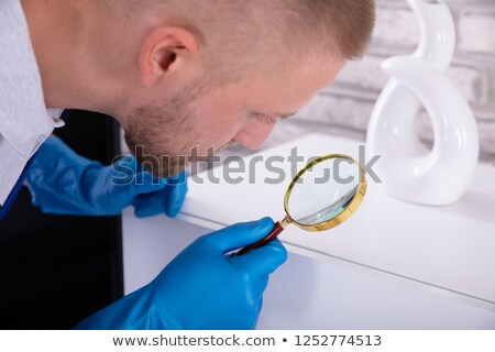 Janitor Examining Cabinet With Magnifying Glass Stock photo © AndreyPopov