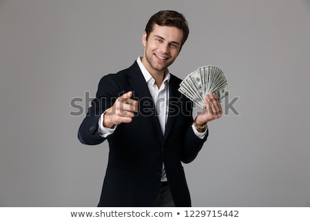 Image of joyful businessman 30s in suit holding fan of money and stock photo © deandrobot