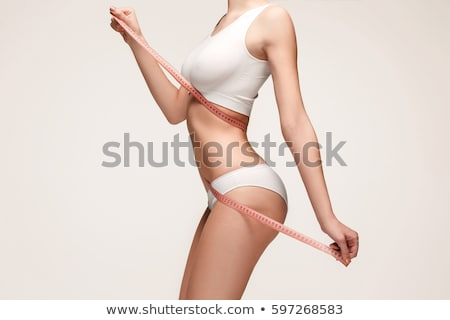 close up of woman body with measure tape on waist stock photo © dolgachov