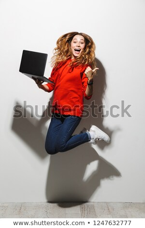 full length photo of excited woman 20s wearing red sweatshirt ho stock photo © deandrobot
