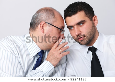 secretive business colleagues whispering in the office stock photo © andreypopov