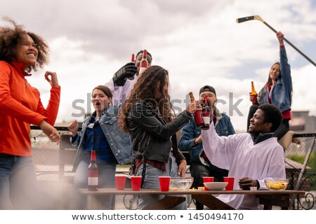 Young intercultural hockey fans celebrating victory of their favorite team Stock photo © pressmaster