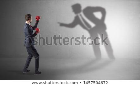 Businessman fighting with his bossy shadow Stock photo © ra2studio