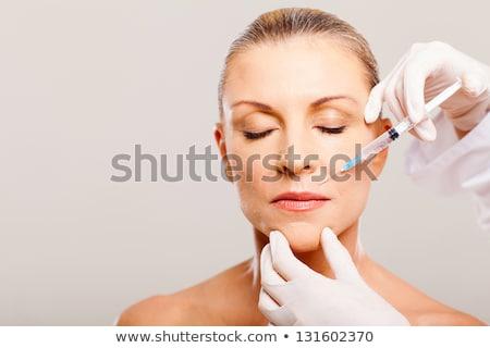 close up of senior woman face and syringe Stock photo © dolgachov