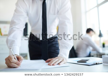 Hands of businessmen bending over financial papers and pointing at information Stock photo © pressmaster
