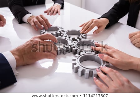 Businesspeople Joining Gears On Desk Stock photo © AndreyPopov