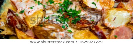 Banner of Oven baked potatoes with cream and cheese in black in a frying pan Stock photo © Illia