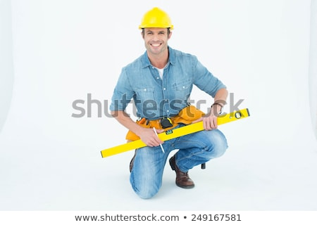 Stock photo: handyman kneeling with spirit level