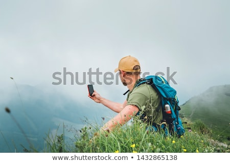 Smiling man photographing with smartphone Stock photo © adamr