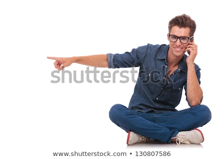 seated man on phone points to side stock photo © feedough