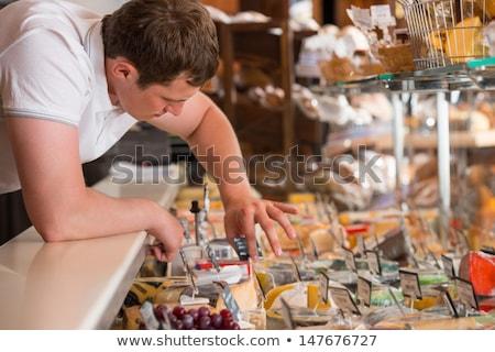 Lojista trabalhando queijo vidro caso mercearia Foto stock © HASLOO