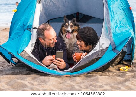 Young Family With Dog Relaxing Inside Tent On Camping Holiday Stock photo © monkey_business