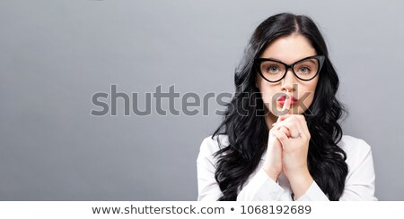 Businesswoman making silence gesture Stock photo © stockyimages