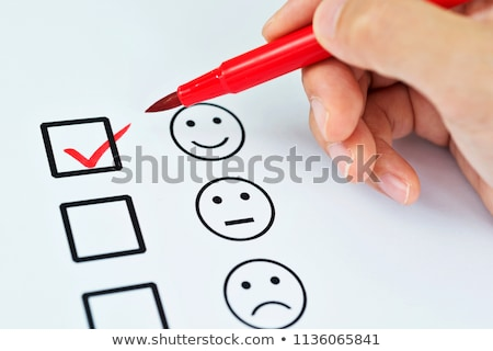 Stock photo: Hand with pen filling out a checklist - Smileys
