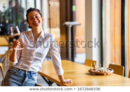 beautiful young brunette holding a glass of red wine stock photo © konradbak