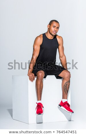 handsome young african sportsman sitting stock photo © deandrobot