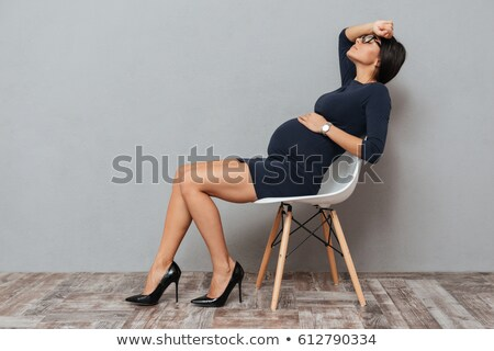 tired pregnant business woman sitting over grey background stock photo © deandrobot
