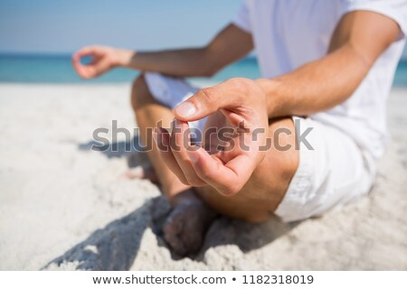 low section of man meditating at beach stock photo © wavebreak_media