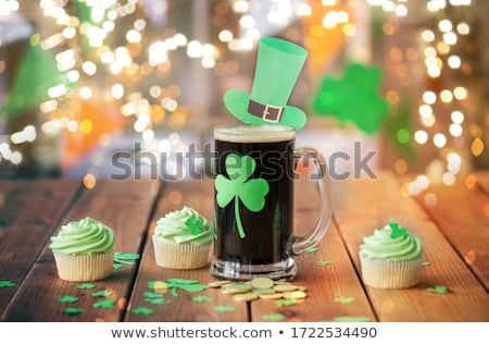shamrock on glass of beer, green cupcakes and coins Stock photo © dolgachov