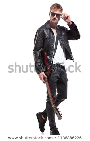 attractive guitarist walks to side and fixes his sunglasses  Stock photo © feedough