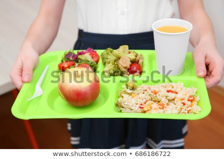 Little girl holding tray with food and drink Stock photo © colematt