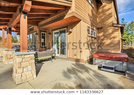 Home exterior with spacious back patio, hot tub and barbecue. Stock photo © iriana88w