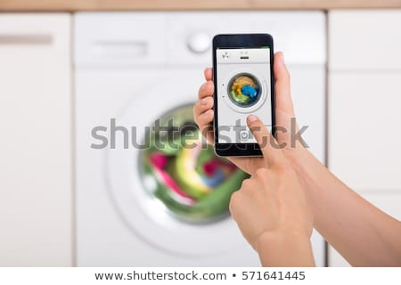 Stock photo: Woman Operating Washing Machine With Cellphone