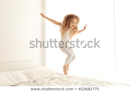 Little girl jumping on the bed Stock photo © colematt