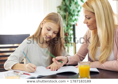 mother helping her daughter during her homework in the living room stock photo © lopolo