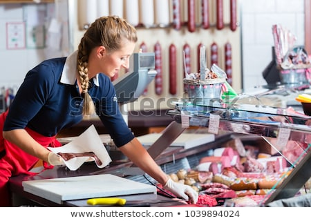 sales woman in butcher shop putting different kinds of meat in display foto stock © kzenon