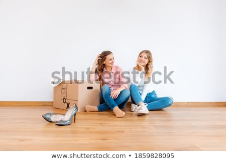 Two women in new apartment dreaming of how to decorate it Stock photo © Kzenon