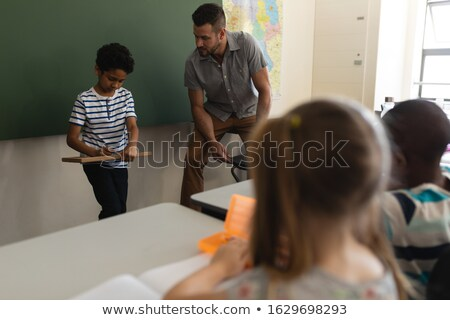 Schoolboy writing on slate board and teacher looking at him in classroom of elementary school Stock photo © wavebreak_media