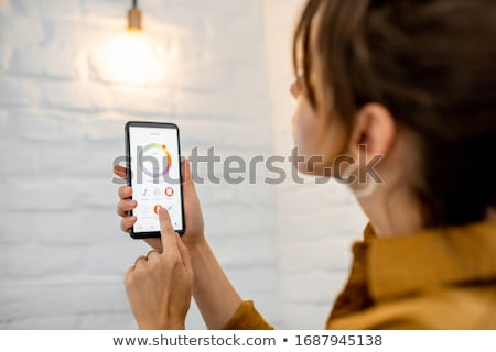 Woman Controlling Electric Lamp With Mobile Phone Stock photo © AndreyPopov