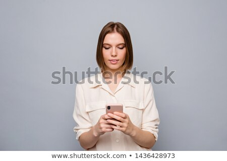 photo of nice fashion woman using cellphones and looking at camera stock photo © deandrobot