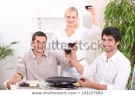 Man enjoying raclette at home with friends Stock photo © photography33