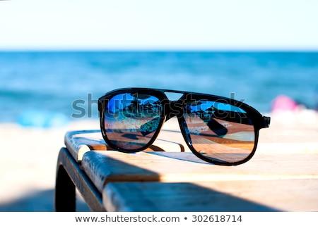 Négy napszemüveg tengerparti nyaralás barátok fény nyár Stock fotó © tannjuska