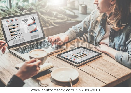 Businesswoman drinking coffee and looking at graphs Stock photo © photography33