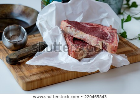 Cuts of raw beef on the cutting board with some green salad in t Stock photo © phila54